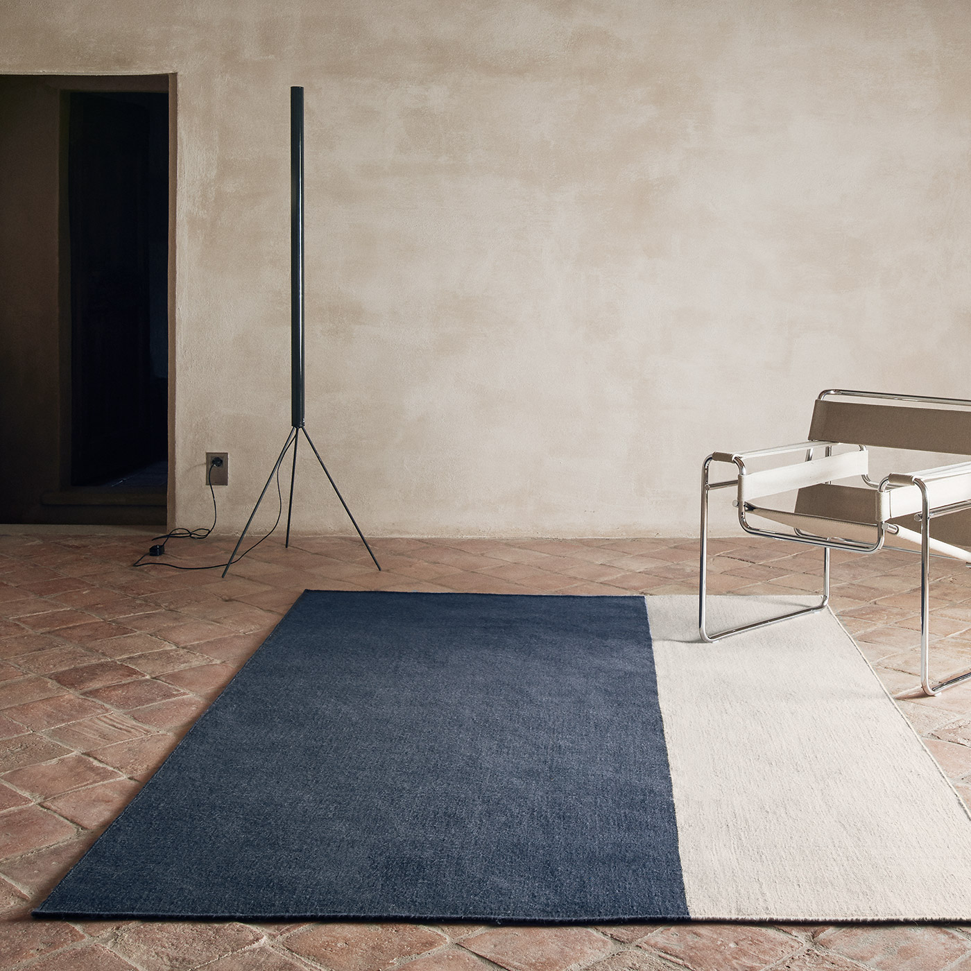 navy and cream two tone rug on rustic tiled floor with modern furniture