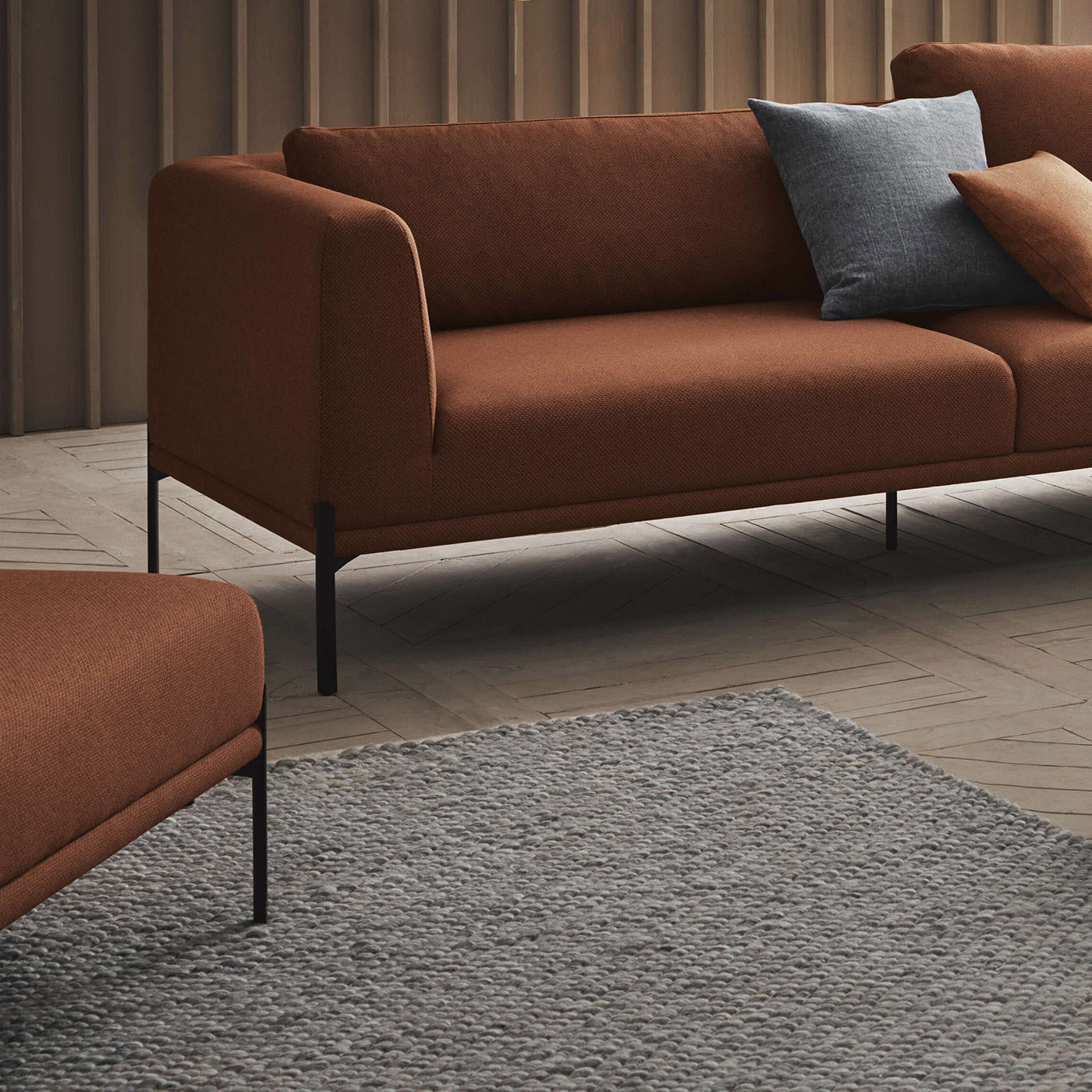 grey chunky woven wool rug and burnt orange sofa