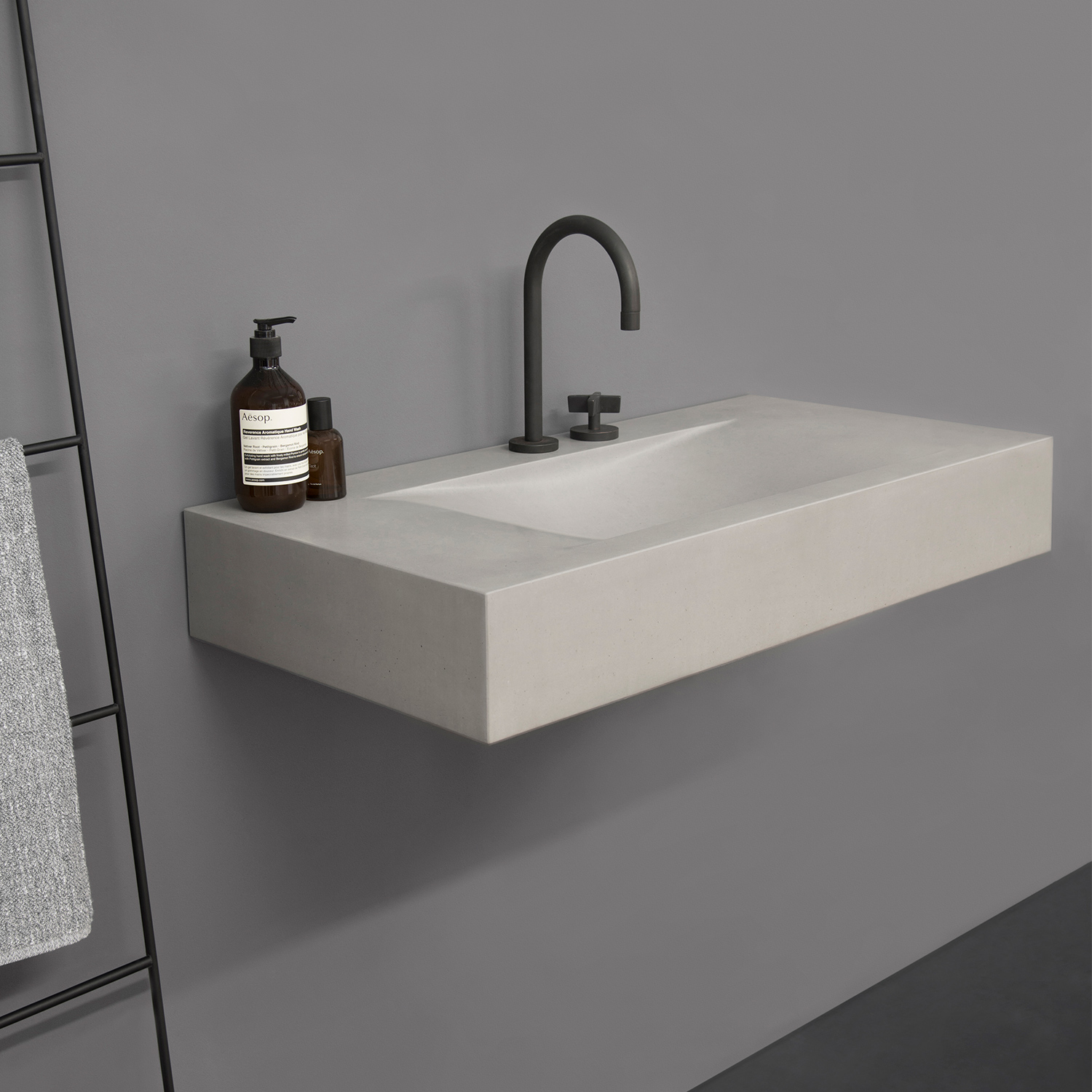 concrete hand basin and black metal mixer tap