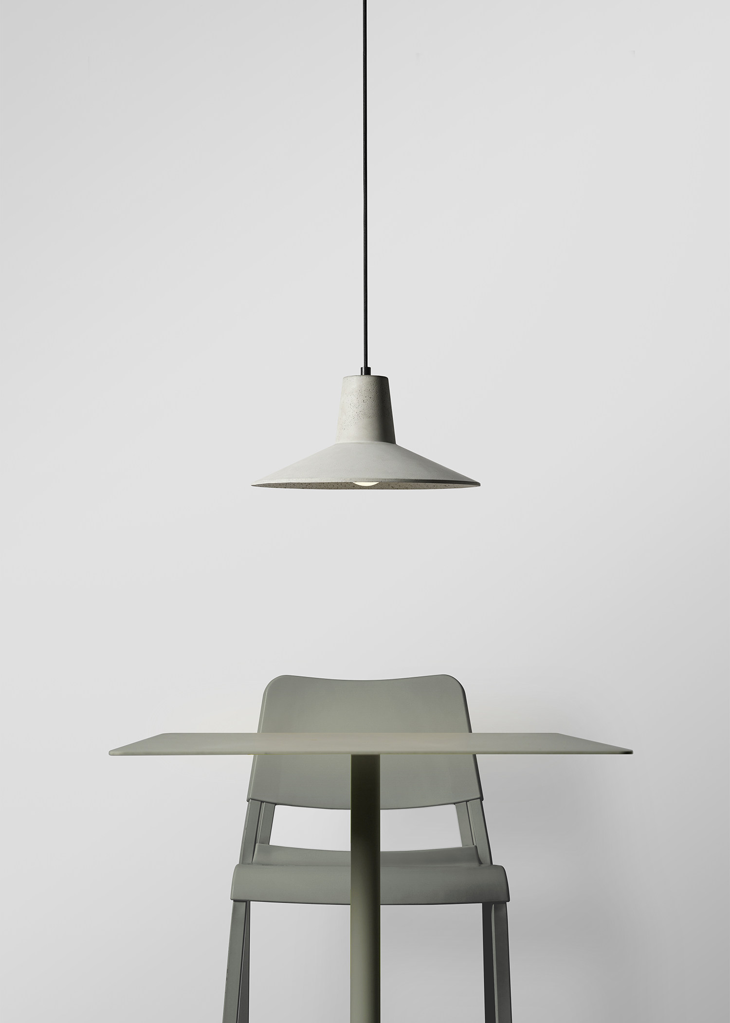 minimal concrete pendant light above sage green metal table and chair