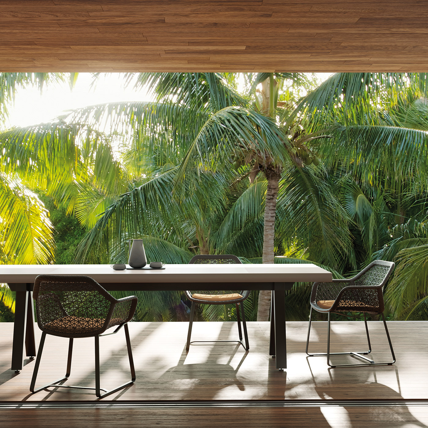 Maia outdoor dining armchair in black mesh with Vieques outdoor dining table in aluminium on a modern teak terrace overlooking palm trees