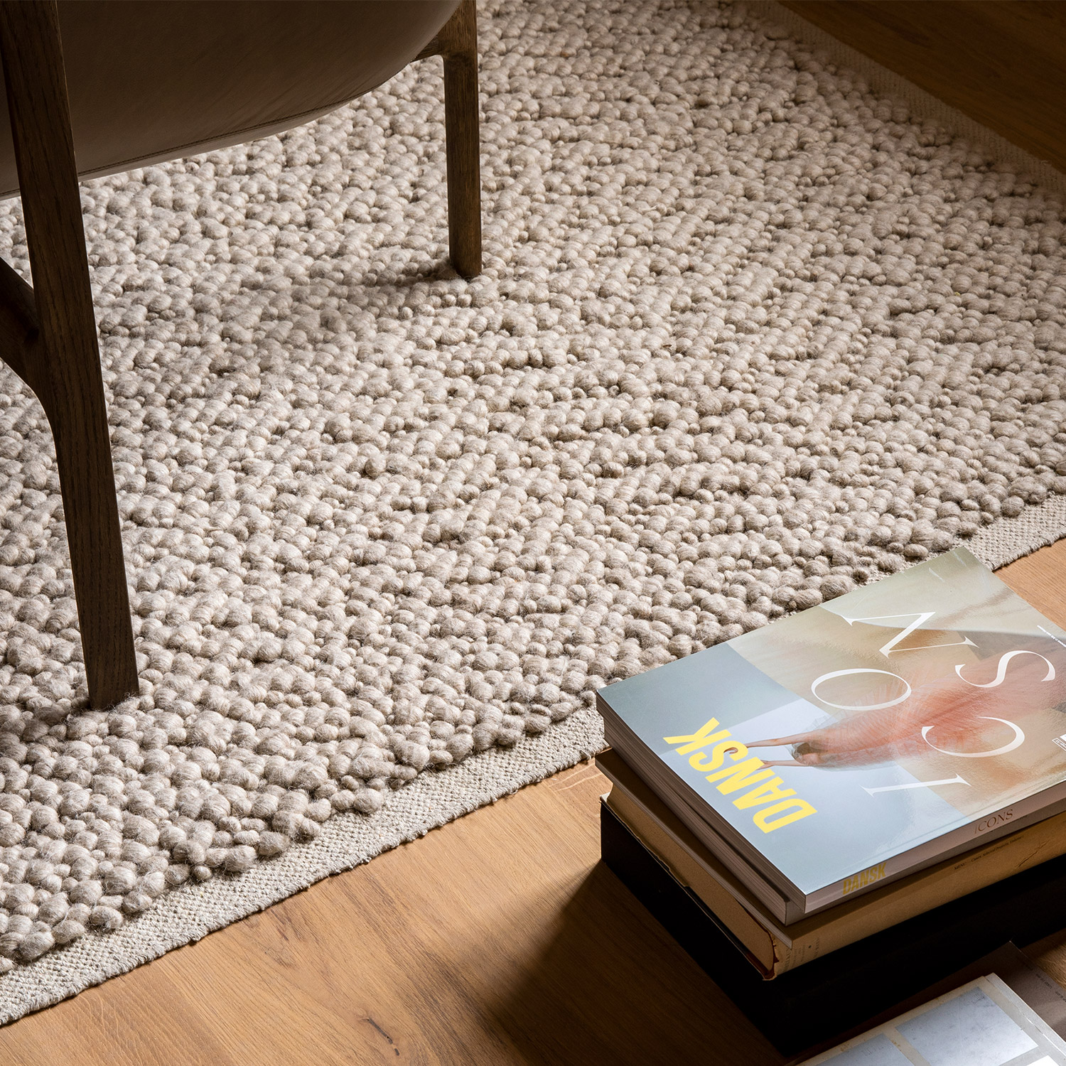 textured cream rug on teak floor with art magazines