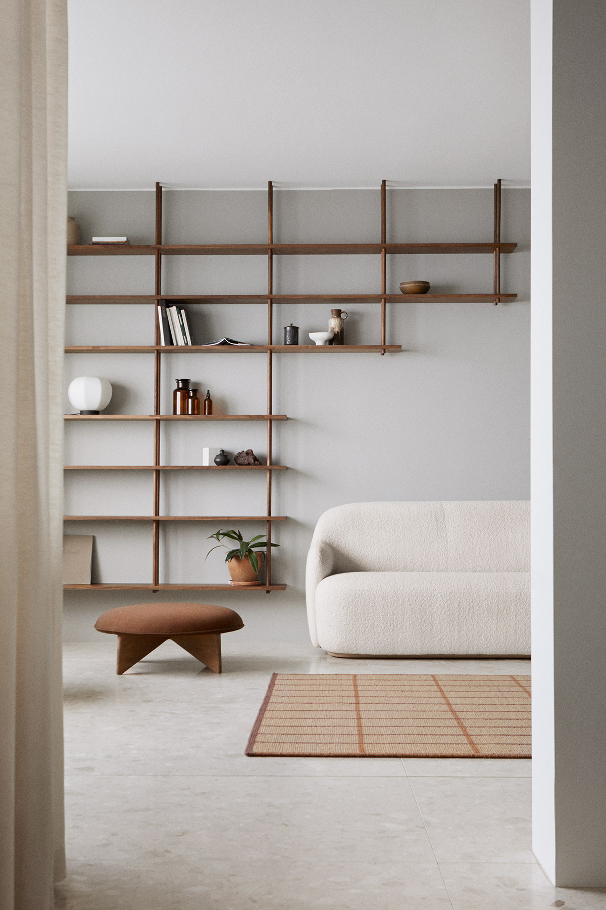 Japanese minimal white living room with white sofa and dark wood shelving