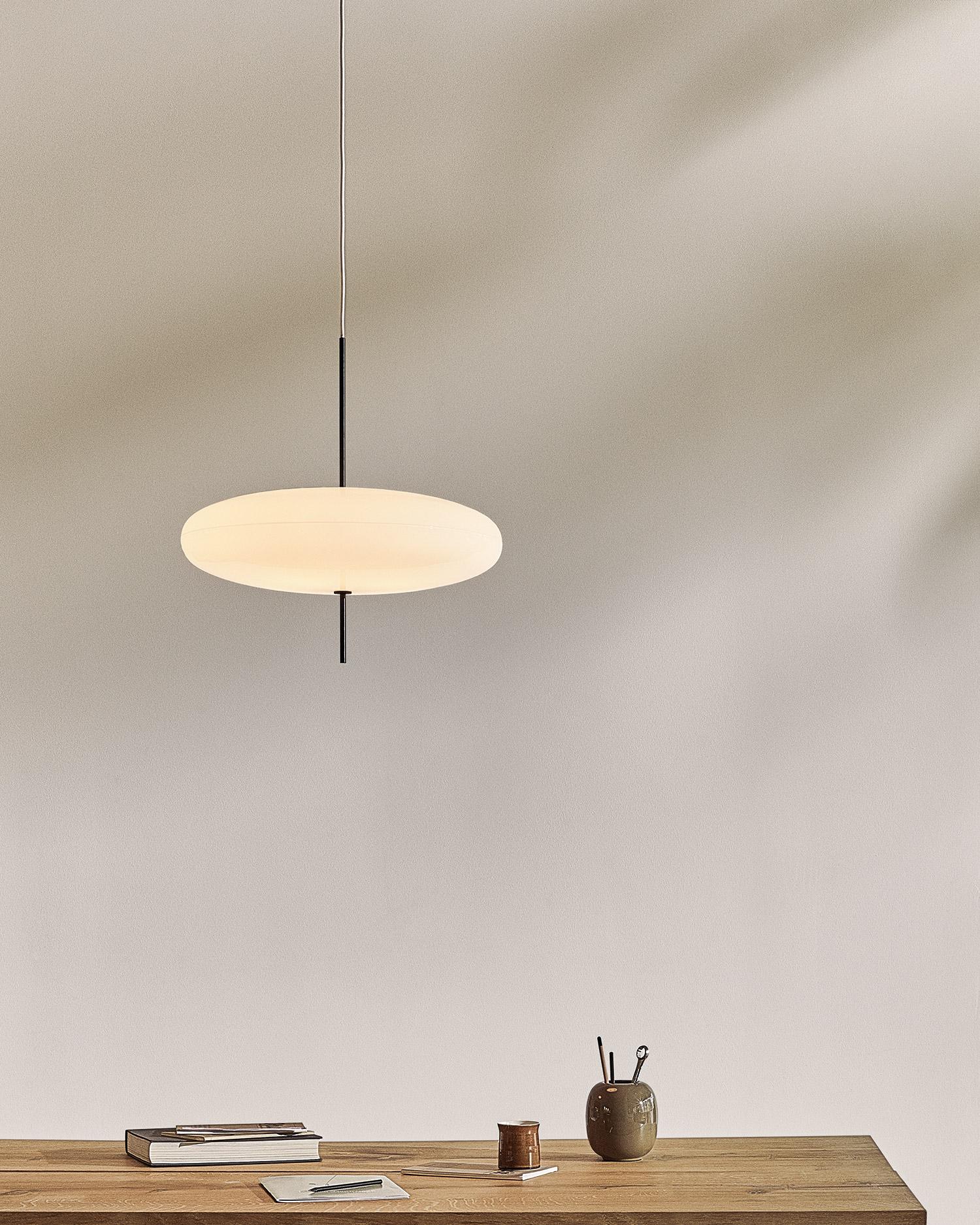 modern minimal pendant light over a wooden desk
