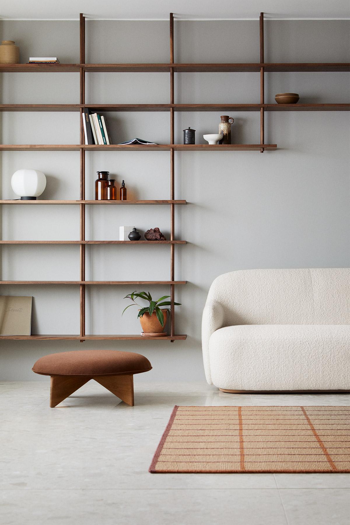 A calm Japanese interior with walnut wood shelving and cream sofa