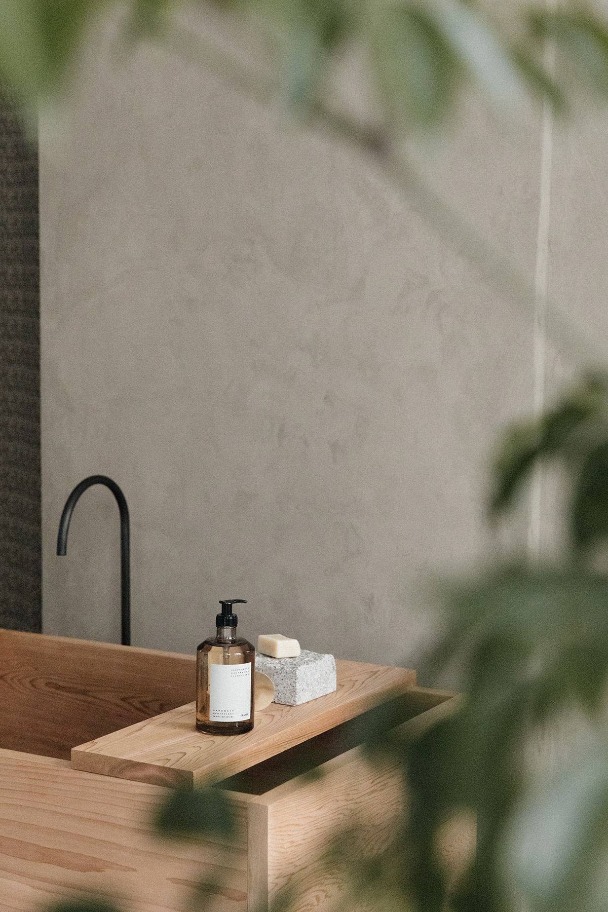 wooden bath tub against raw rendered wall surrounded by tranquil plants