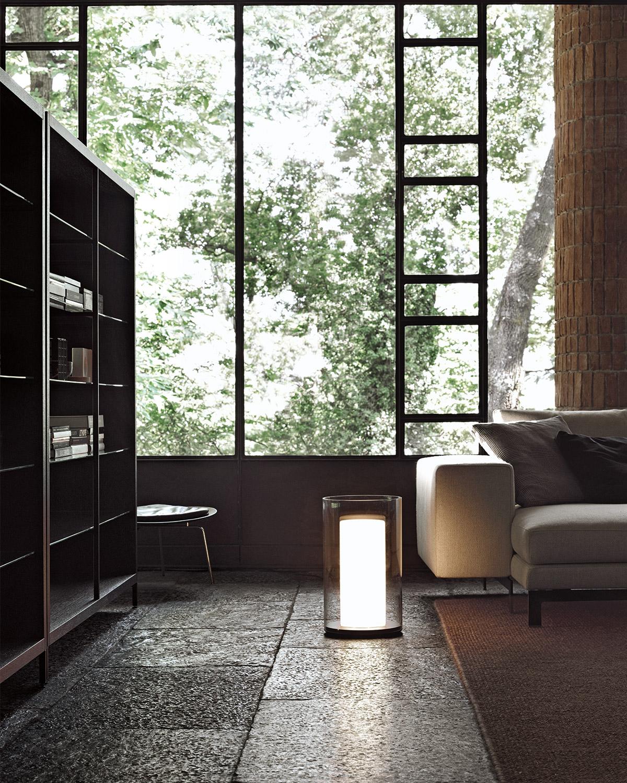 modern Italian interior with floor to ceiling windows, minimal sofa and bookshelves and floor lamp