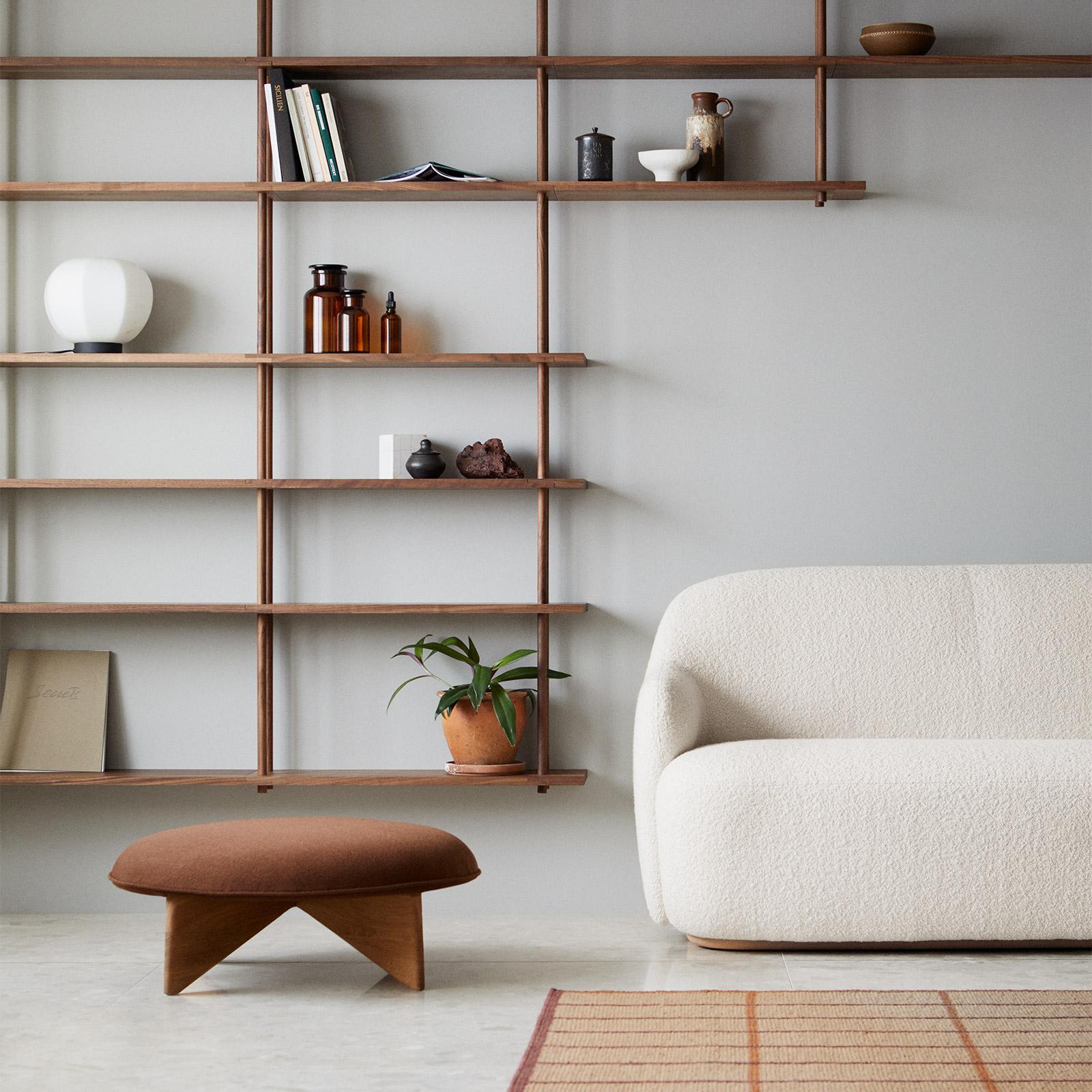 dark wooden shelves against a white wall with a modern white sofa