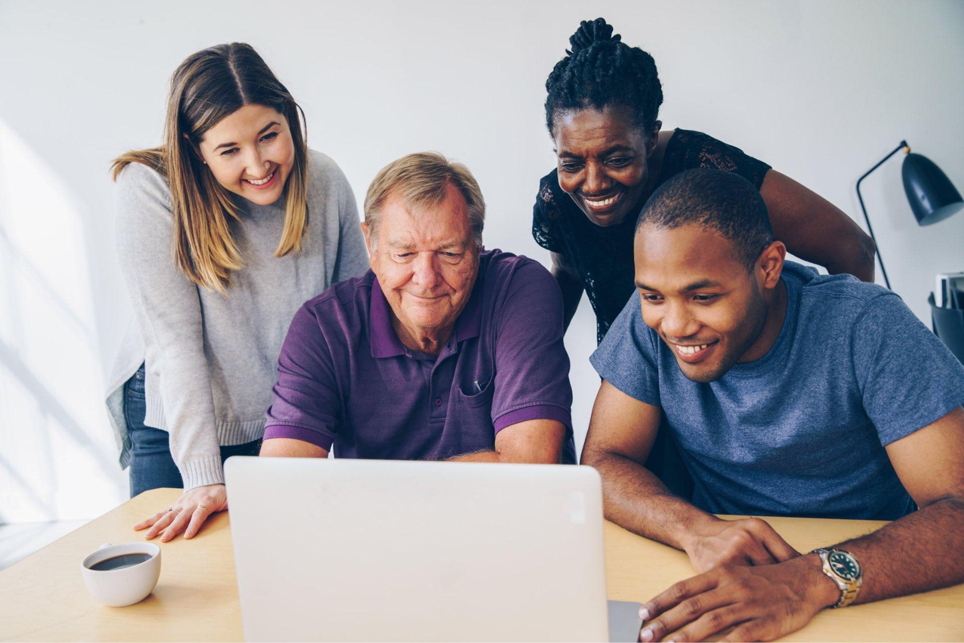 Quatro pessoas de diferentes idades e sexo olhando para a tela de um notebook.