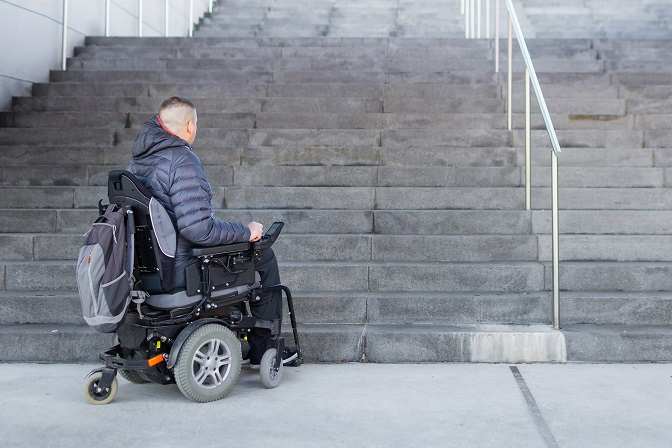 man in wheelchair at bottom of steps without a ramp