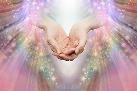 Healing hands surrounding by warm, shining rays of light.