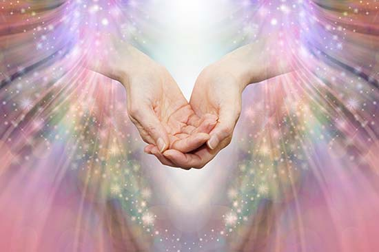 Healing hands hover over a backdrop of stars, surrounding by warm, shining rays of light.