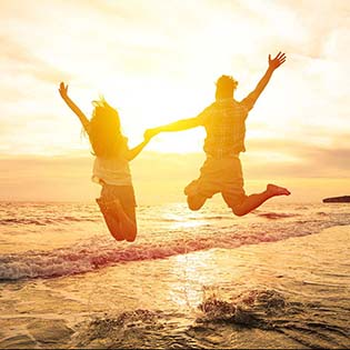 A couple holds hands and jumps for joy in the golden glow of sunset at the beach.