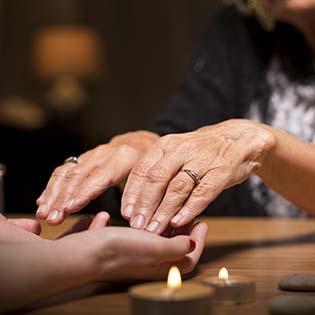 An older woman touches hands with a younger woman during a psychic reading.