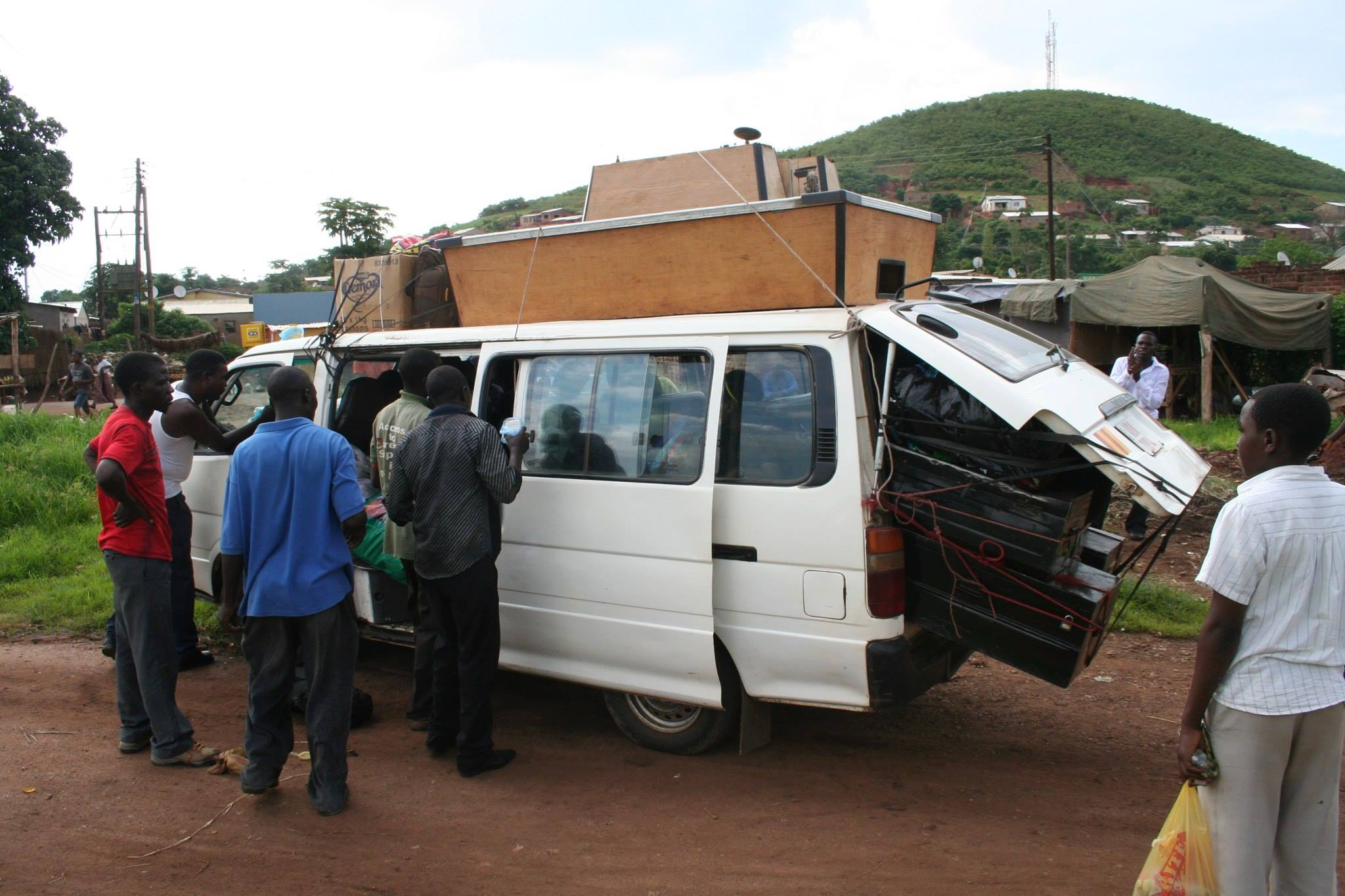 Crowded bus in Zambia with billiards table on roof