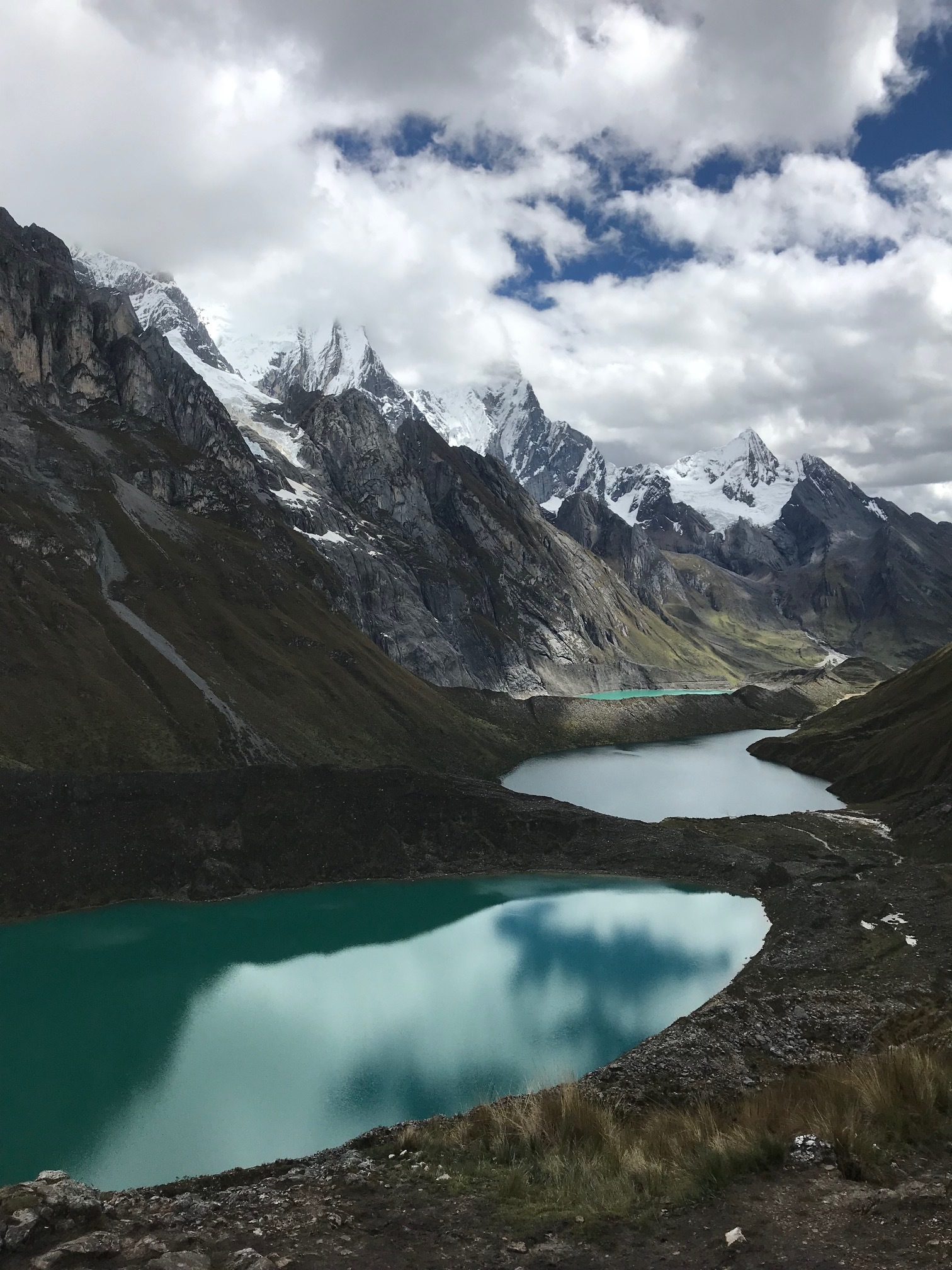 2 green lakes in a valley of snow capped mountains