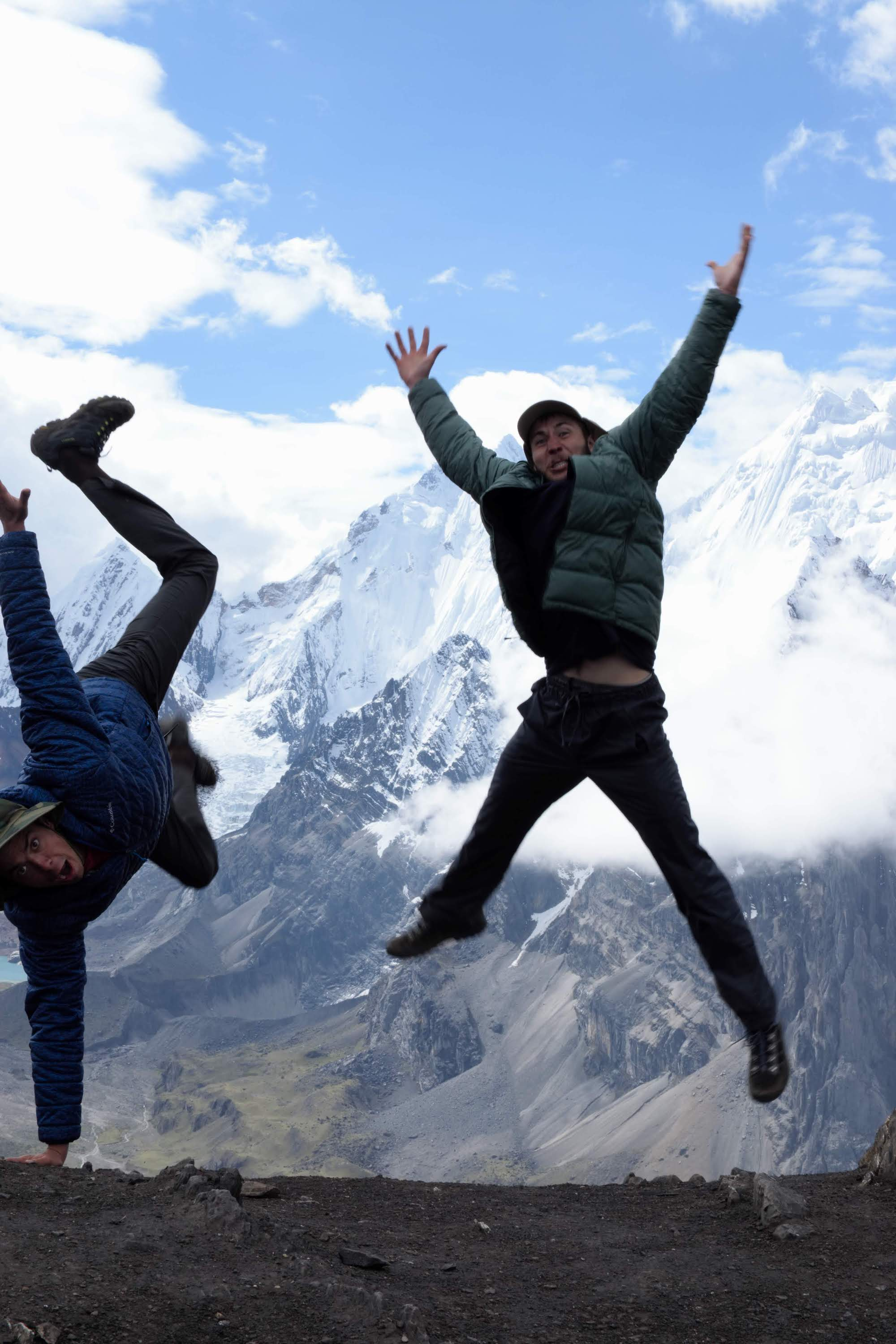 Jack and Max jumping for a photo with a mountain in the background