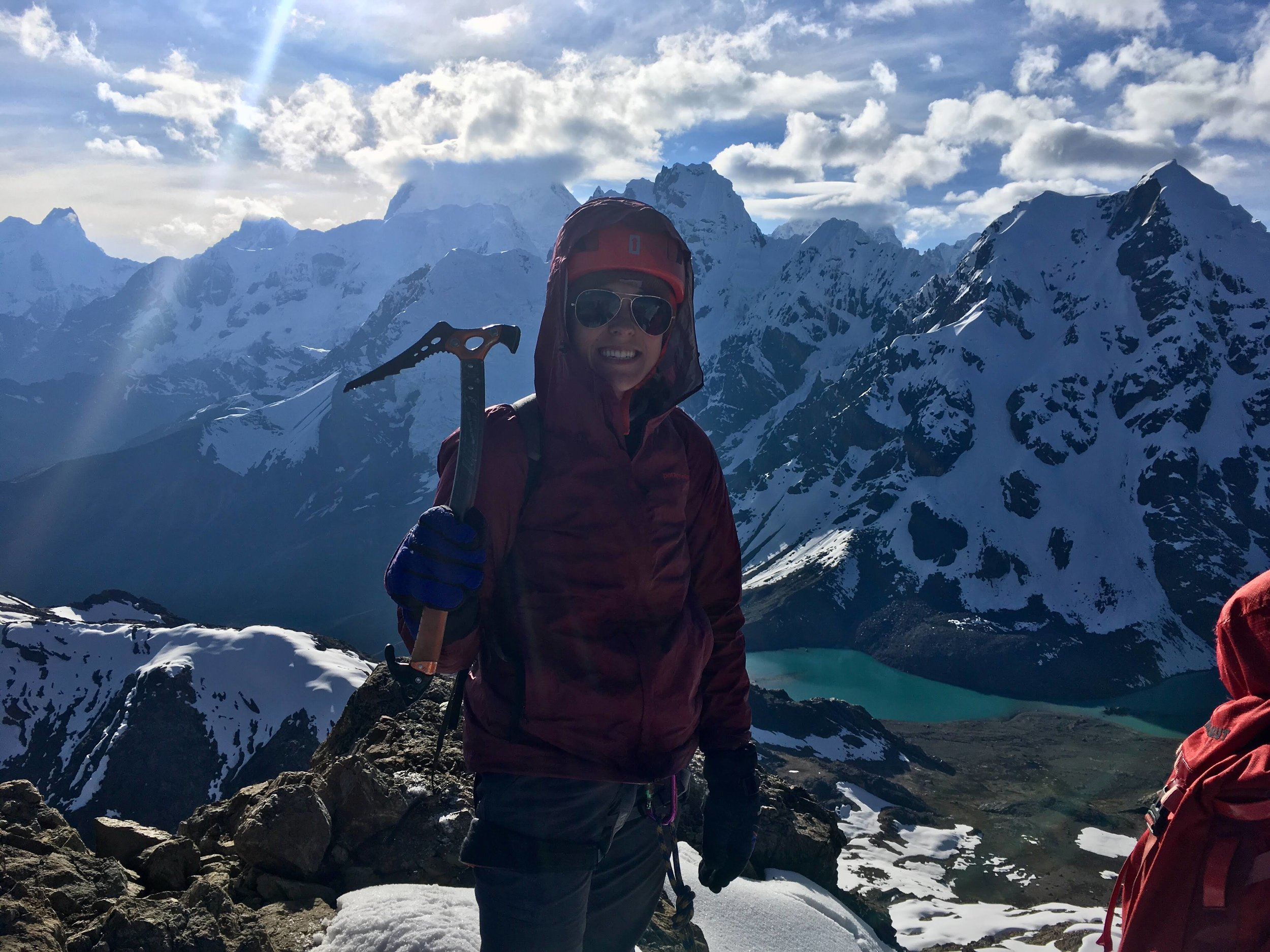 Taylor holding an ice pick and smiling atop the mountain