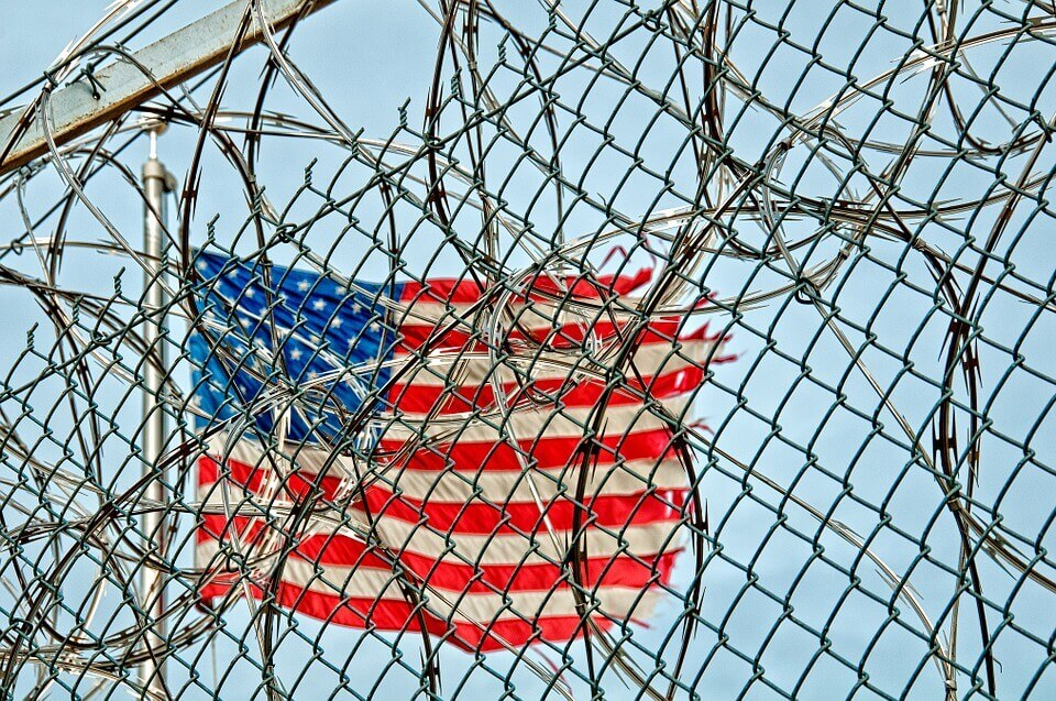 The United States flag behind a chainlink fence