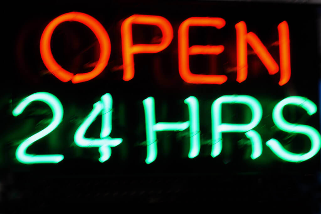 """A neon sign that says """"Open 24 hours"""""""