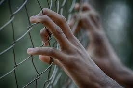 A man holding onto a chainlink fence