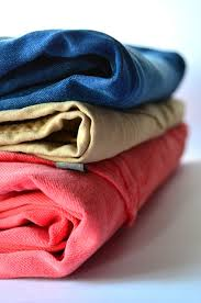 Folded stacked clothing. Blue jeans on top of a yellow shirt on top of a red sweatshirt.