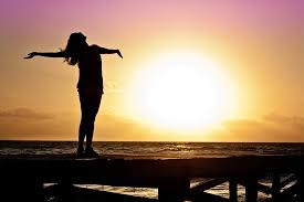 A woman posing in front of a sunset