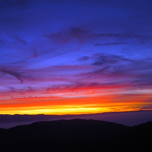 A brilliant red sunset over the rounded tops of mountains, seen from a high elevation