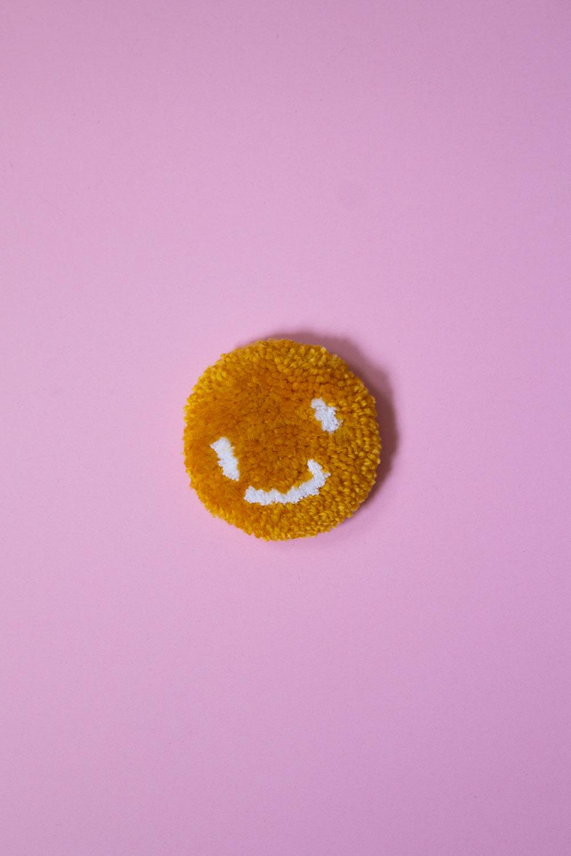 Mini tapis touffeté à la machine avec une épingle à l'arrière pour en faire un macaron / Smiley face jaune moutarde / fait avec amour à Montréal par Audrey Lord / laine en acrylic et cotton / pièce unique, c'est le seul ainsi en vente!!! / dimension: 3x3 po / Cette pin est parfaite pour décorer ton sac à dos ou ton coat de jeans sans engagement!!