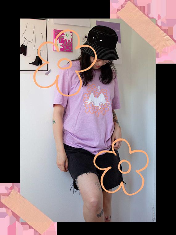 Photo d'Audrey qui porte le t-shirt lilac minou dans les fleurs, taille medium, légèrement oversize sur elle.