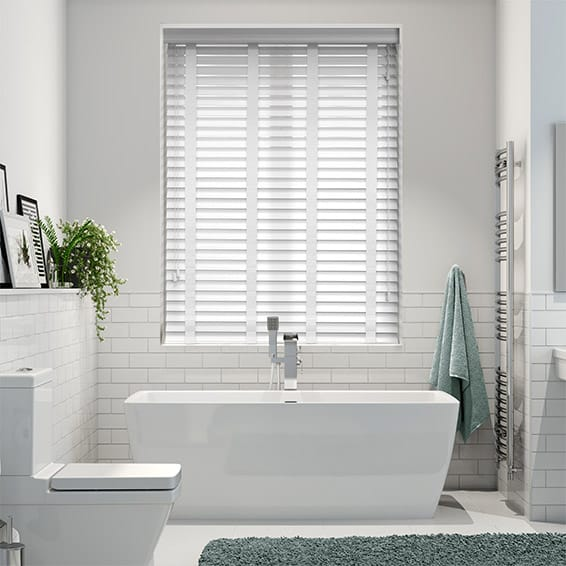 white faux wood venetian positioned over bath