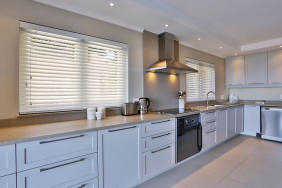 wooden venetian blinds fitted on dual windows in a traditional white kitchen