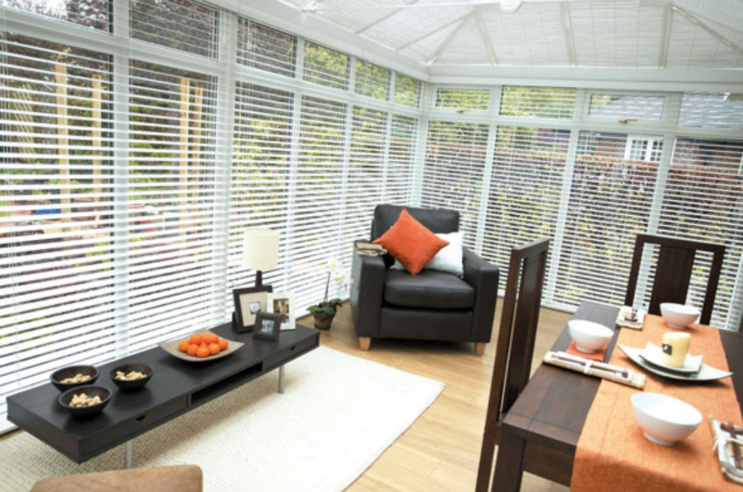 White full length wooden venetian blinds fitted in a conservatory