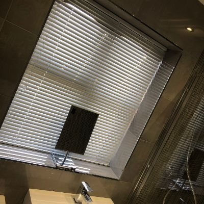shiny white aluminium venetian blind fitted in bathroom