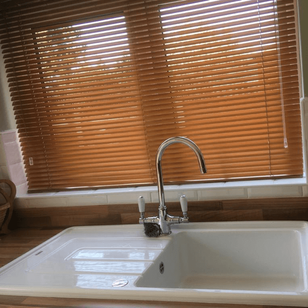 Copper metal venetian blind fitted above sink