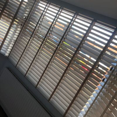 white faux wood blinds with contrasting tapes in living room bay