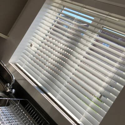bright white faux wood blind fitted in kitchen