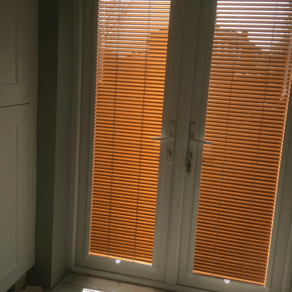 A copper orange finish to metal venetian blinds