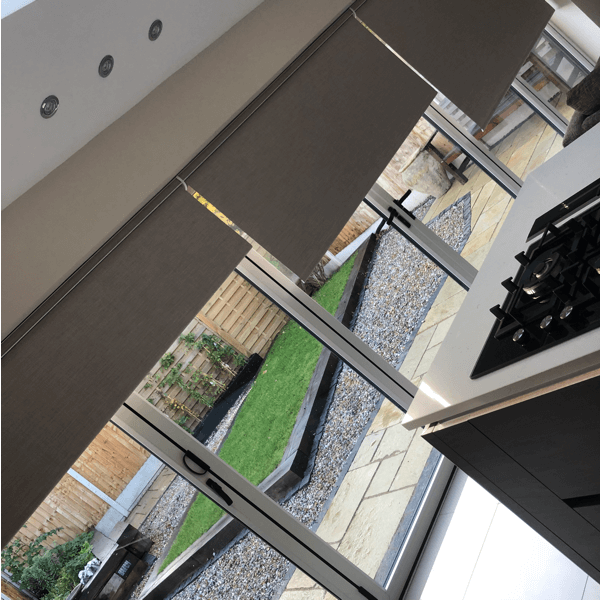 Grey roller blinds with remote control system in kitchen