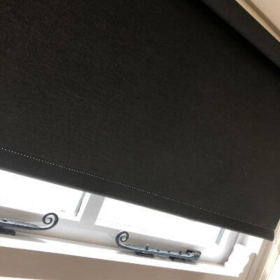 Black roller blind fitted on traditional cottage style window