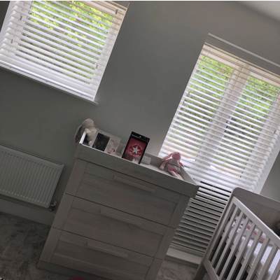 white faux wood blinds with child safety features in nursery