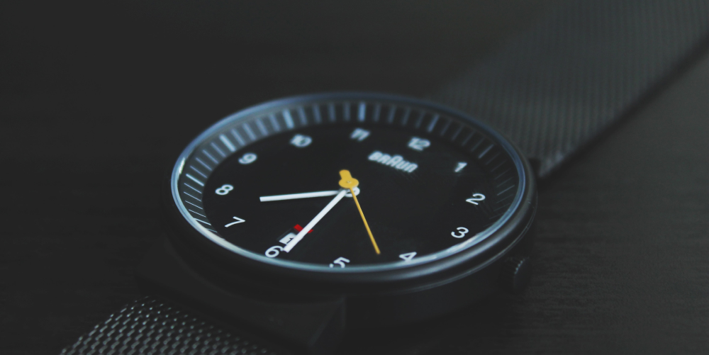 simple black watch with yellow seconds hand on black background