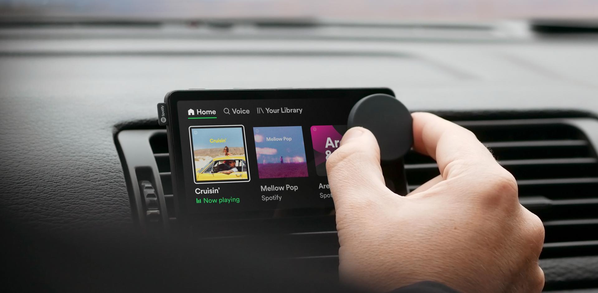 Man turning control wheel on spotify car thing