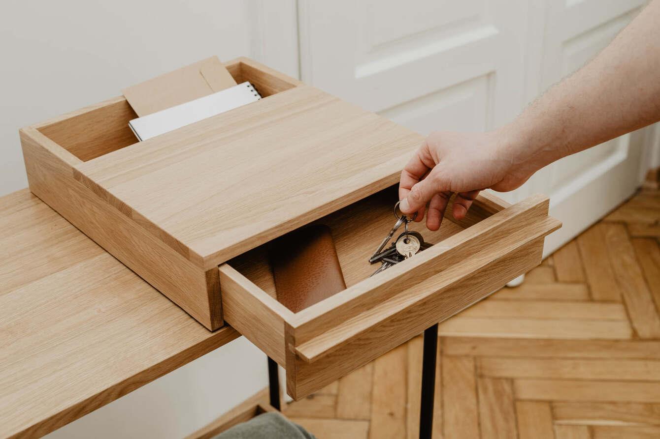 Man putting keys into an open drawer