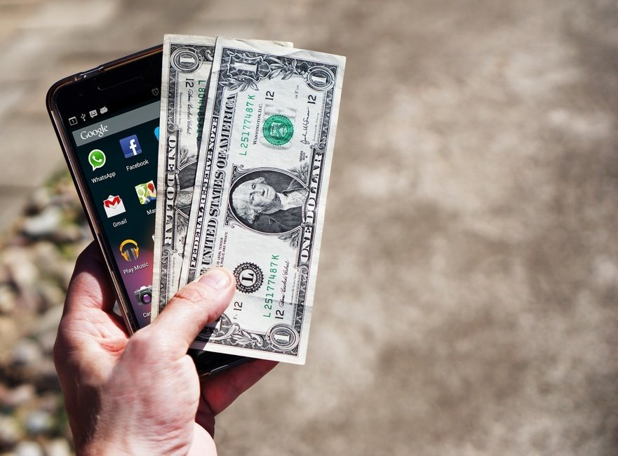 an android phone with 2 one dollar bills