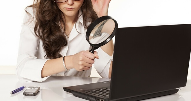 a woman using magnifying glass on her laptop
