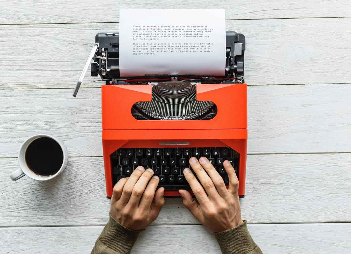 a person typing on his typewriter with a glass of coffee beside him