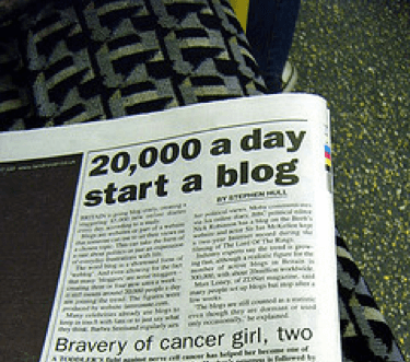 A newspaper headline with text of 20,000 a day start a blog