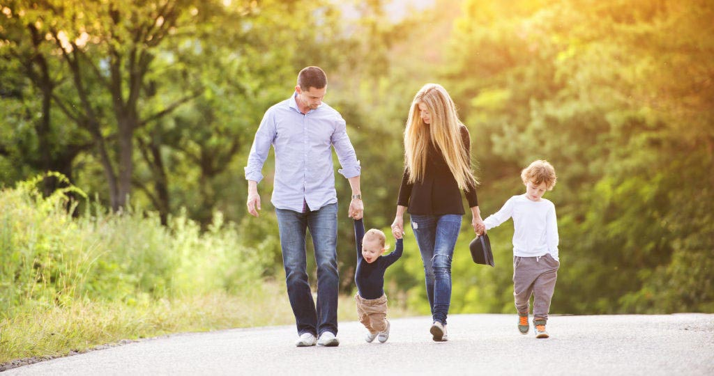 A family consists of mother, father with 2 kids having a walk in the park