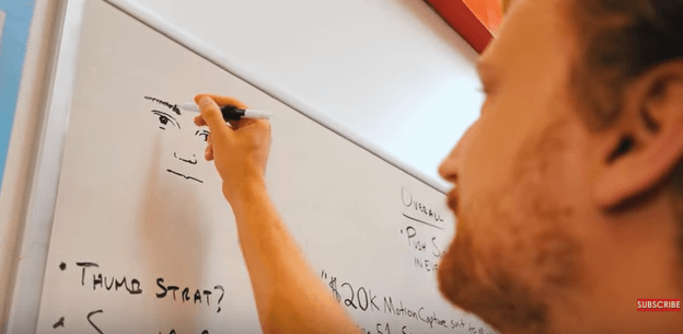 A man drawing a face on a whiteboard with marker